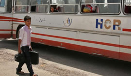 A boy with suitcase boarding a bus to leave the UNHCR voluntary repatriation centre in Dogharoun.