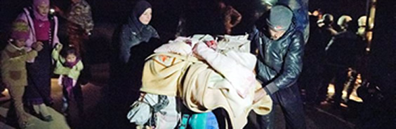 A man uses a stroller to carry his posessions across the Syrian border at night