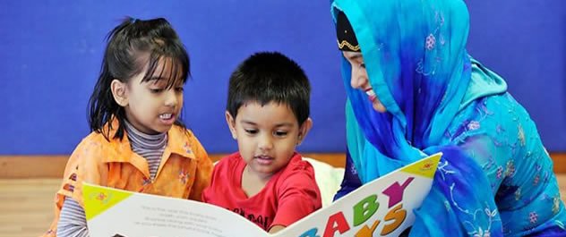 Woman reading a picture book with 2 young children