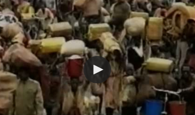 crowd of people carrying water containers on shoulders